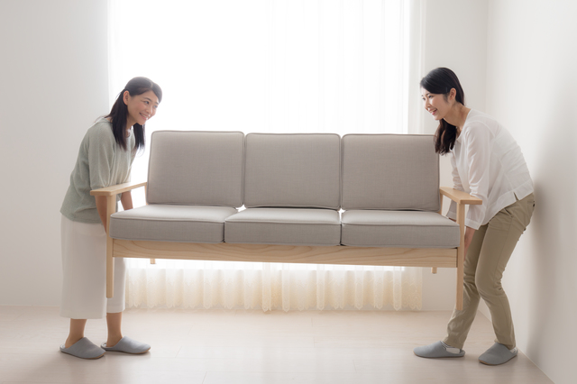 女性が家具を運んでいる写真